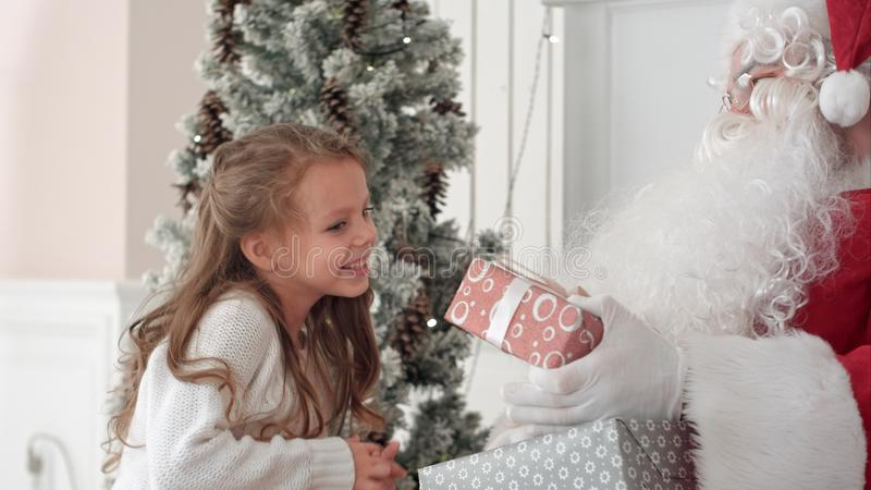 Święty Mikołaj ściska troszkę ślicznej dziewczyny i daje jej Bożenarodzeniowej teraźniejszości zdjęcia royalty free