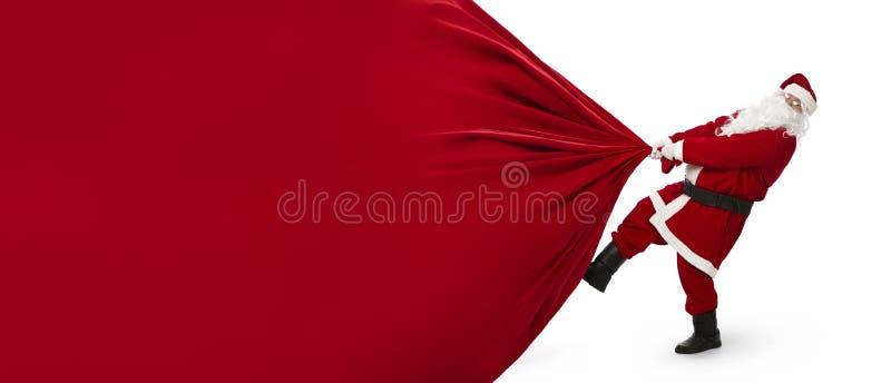 Święty Mikołaj ciągnie ogromną torbę prezenty fotografia stock