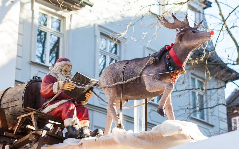 Święty Mikołaj czyta książkę na saneczki z reniferem zdjęcie royalty free