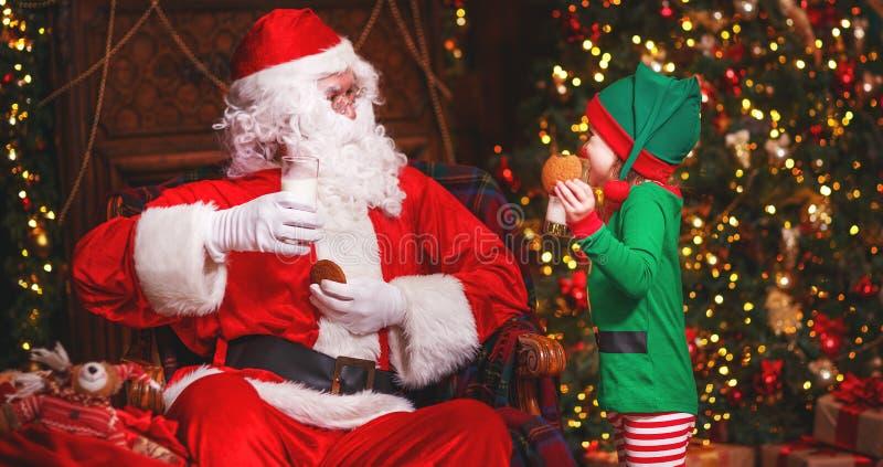 Święty Mikołaj i elfa dziecko w łasowania Bożenarodzeniowych pije dojnych ciastkach zdjęcia royalty free