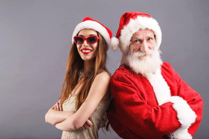 Święty Mikołaj I Młody Mrs Claus pozycja i ono Uśmiecha się Na Popielatym tle zdjęcia stock