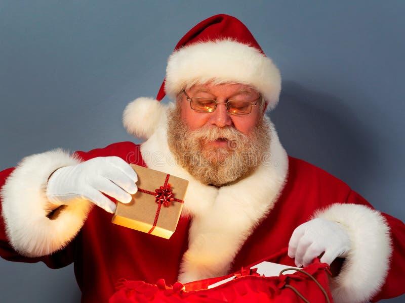 Święty Mikołaj kładzenia prezenty w jego grabiją zdjęcia royalty free
