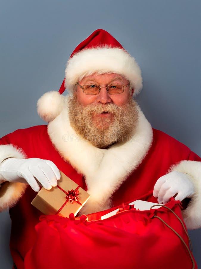 Święty Mikołaj kładzenia prezenty w jego grabiją obraz stock
