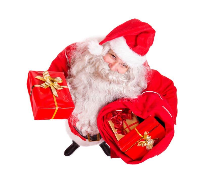 Święty Mikołaj mienia Bożenarodzeniowi prezenty z torbą obraz stock