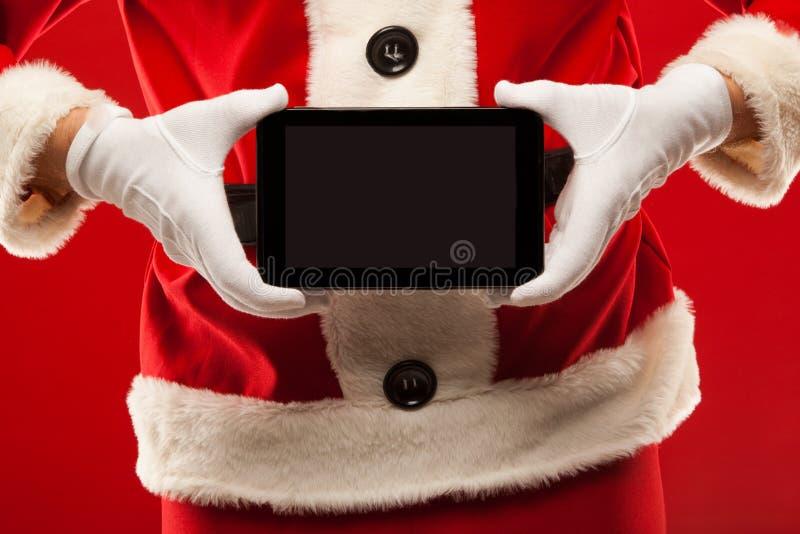 Święty Mikołaj mienia pastylka czerwony tło, ręki zdjęcia stock
