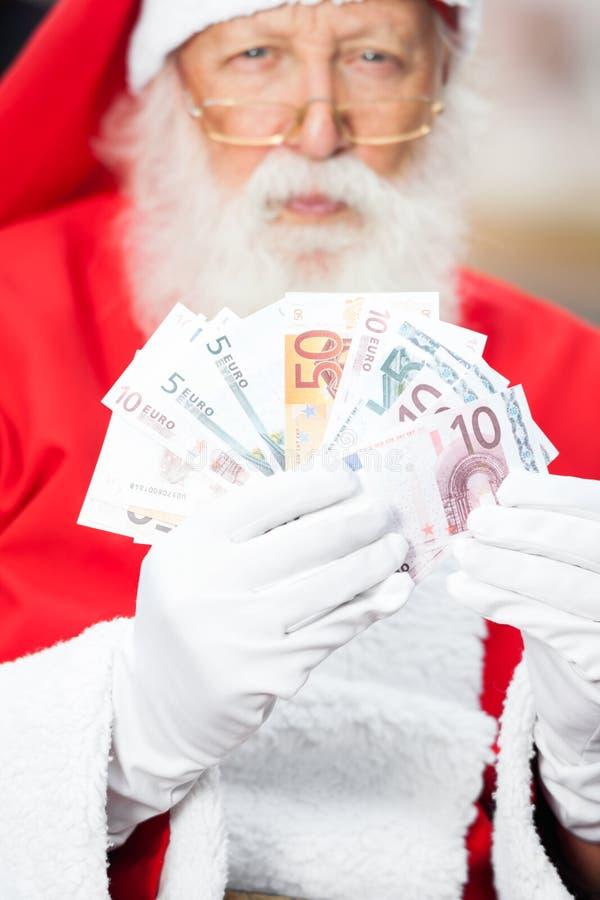 Święty Mikołaj mienia pieniądze zdjęcie stock
