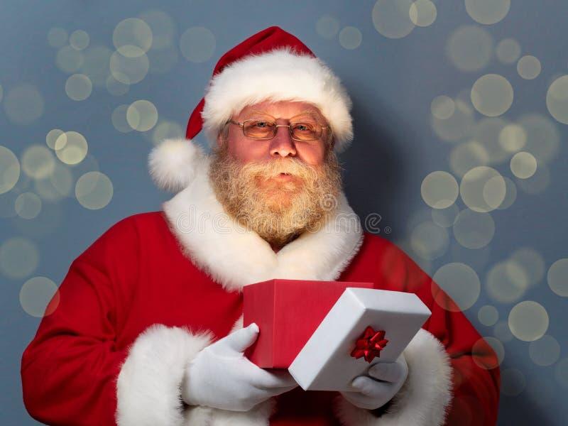 Święty Mikołaj mienia prezenta rozpieczętowany pudełko obraz stock