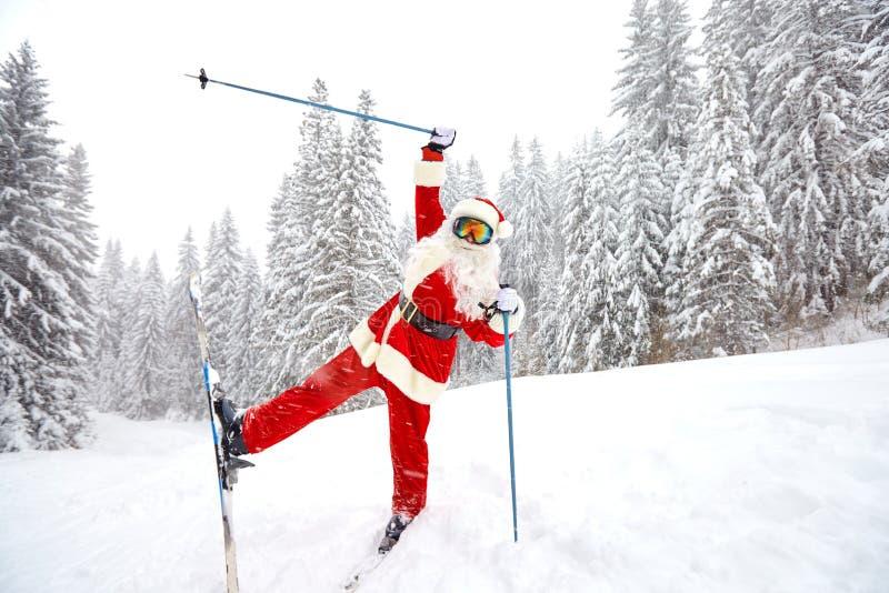 Święty Mikołaj narciarstwo w górach na śniegu w zimie w Christm fotografia stock