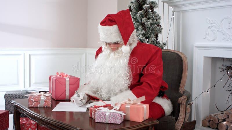 Święty Mikołaj narządzania teraźniejszość dla dzieci i sprawdzać prezent listę fotografia stock