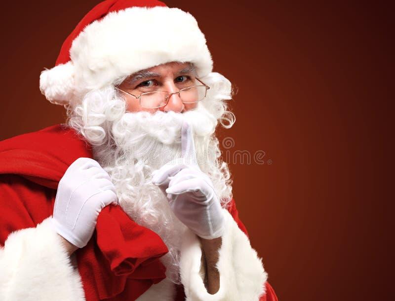 Święty Mikołaj niesie ogromnego czerwień worek i pokazuje gest cisza zdjęcie stock