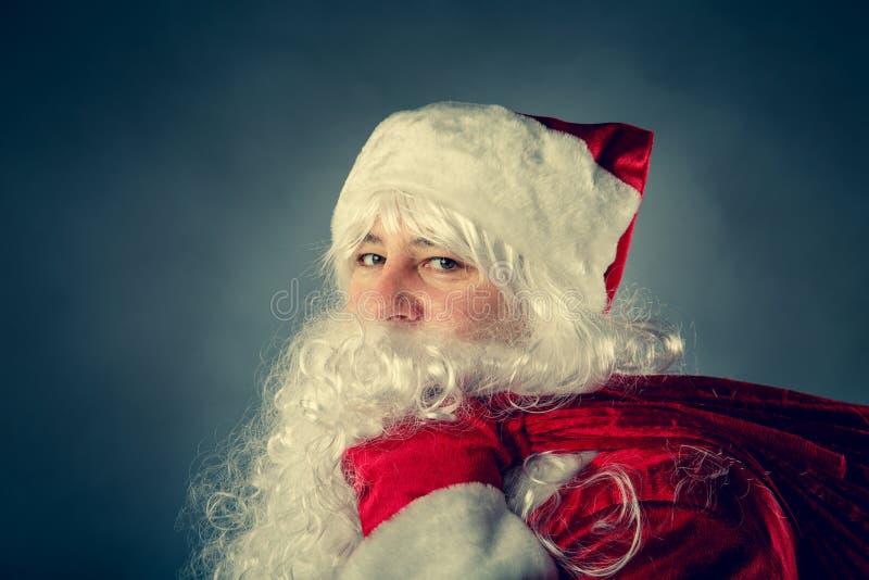 Święty Mikołaj niesie torbę z prezentami zdjęcie royalty free