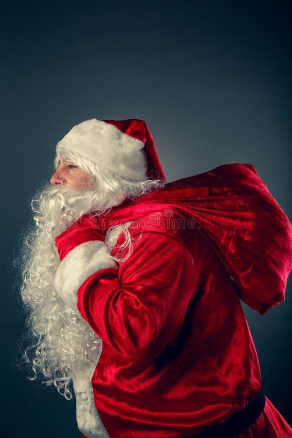 Święty Mikołaj niesie torbę z prezentami obraz stock