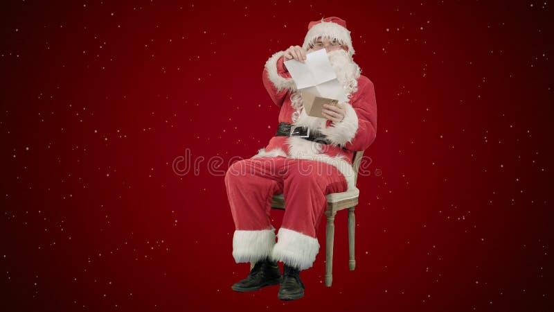 Święty Mikołaj obsiadanie na krześle z listami w rękach na czerwonym tle z śniegiem zdjęcia royalty free