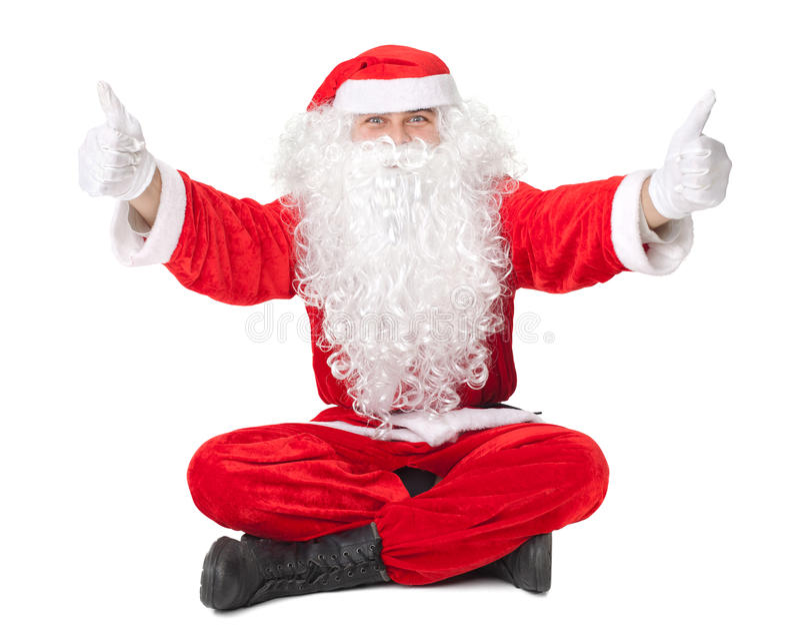 Święty Mikołaj obsiadanie na podłoga z kciukiem up podpisuje fotografia stock