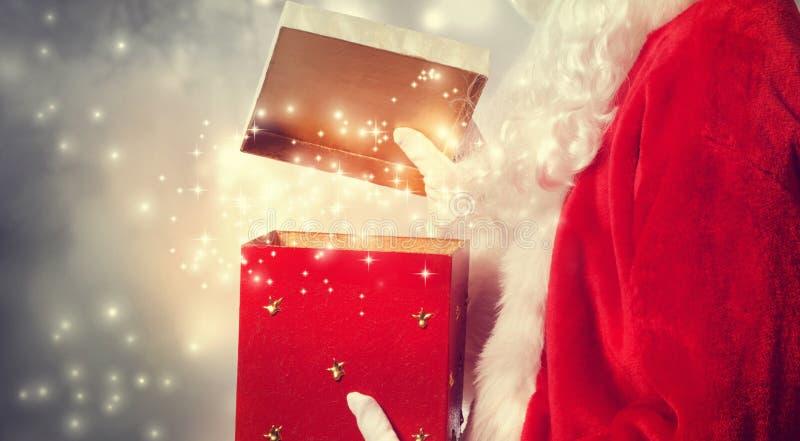 Święty Mikołaj Otwiera Czerwoną Bożenarodzeniową teraźniejszość obrazy royalty free