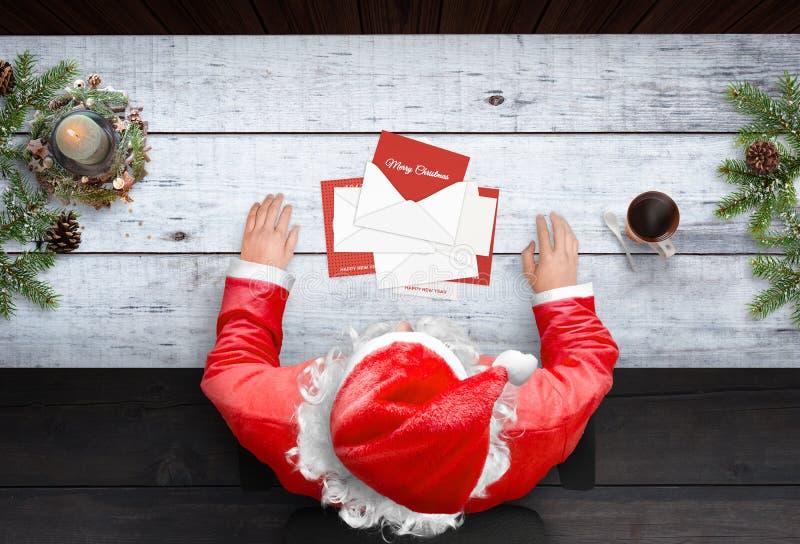 Święty Mikołaj otwiera kartki z pozdrowieniami i listy na pracy biurku obrazy stock