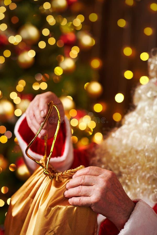 Święty Mikołaj otwiera torbę prezentów, siedząc w pomieszczeniu obok dekorowanego drzewa świątecznego ze światłami - Wesołych Świ fotografia stock