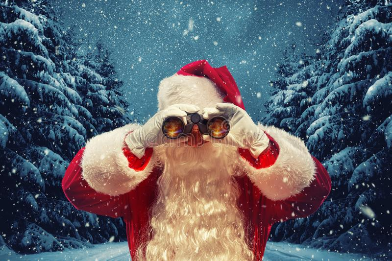 Święty Mikołaj patrzeje przez lornetek Bożenarodzeniowy pojęcie zdjęcie stock