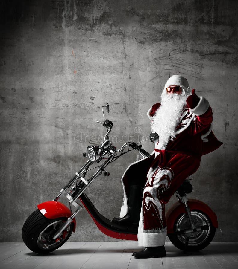 Święty Mikołaj przedstawienia aprobat szyldowy obsiadanie na elektrycznego motocyklu rowerowej hulajnodze z tekst kopii przestrze zdjęcia stock