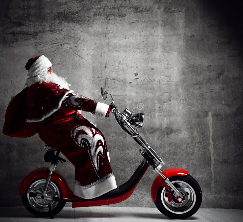 Święty Mikołaj przejażdżki motocyklu rowerowa hulajnoga z torbą pełno teraźniejsi prezenty z tekst kopii przestrzenią Nowy Rok i  obrazy stock