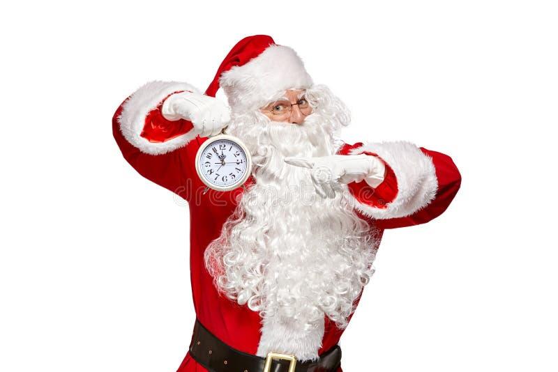 Święty Mikołaj punktów palec przy zegarem Bożenarodzeniowy pojęcie obrazy stock