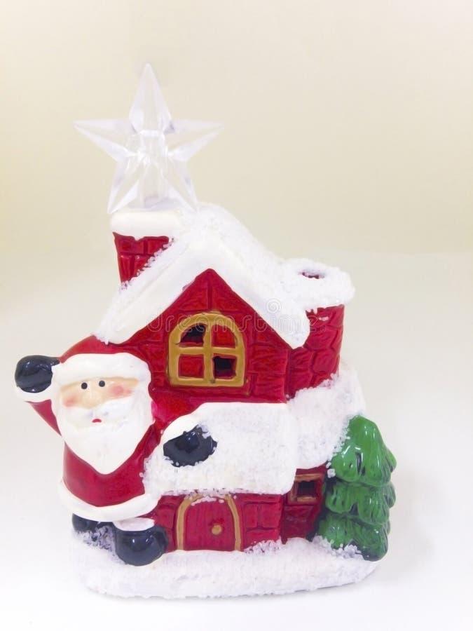 Święty Mikołaj ` s ceramiczny dom zakrywa z śniegiem, odizolowywającym na wh fotografia royalty free