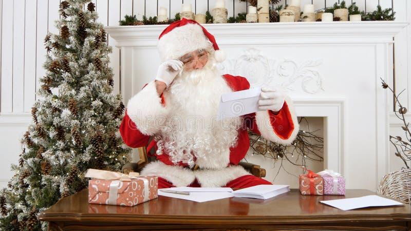 Święty Mikołaj sortuje out papierowych listy od dzieci obraz stock