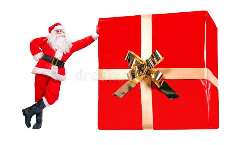 Święty Mikołaj stoi bezczynnie wielkiego Bożenarodzeniowego prezent obrazy royalty free