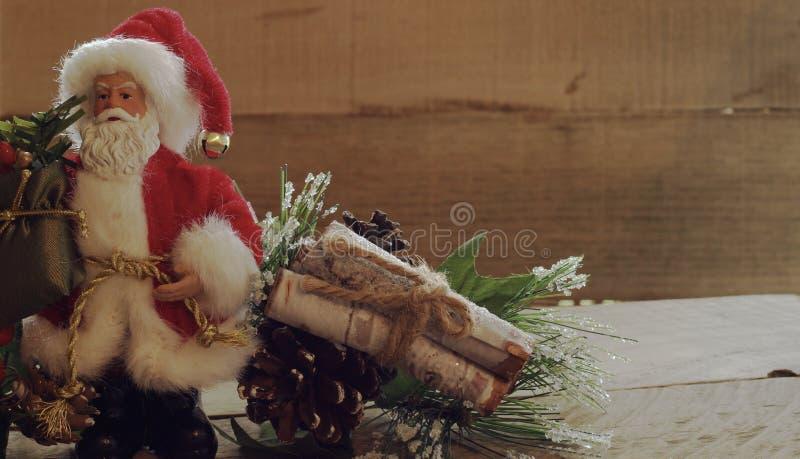 Święty Mikołaj stoi następnego greenery z drewnem loguje się plika na drewnianym tle obrazy stock