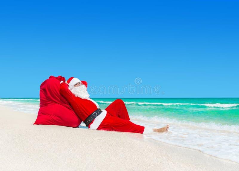 Święty Mikołaj sunbathe na Bożenarodzeniowych prezentach grabije przy ocean plażą fotografia royalty free