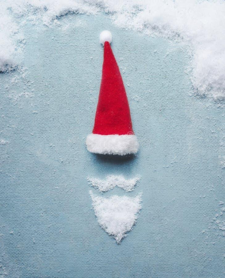 Święty Mikołaj symbol robić z śniegiem i Santa kapeluszem na błękitnym tle więcej toreb, Świąt oszronieją Klaus Santa niebo obrazy stock