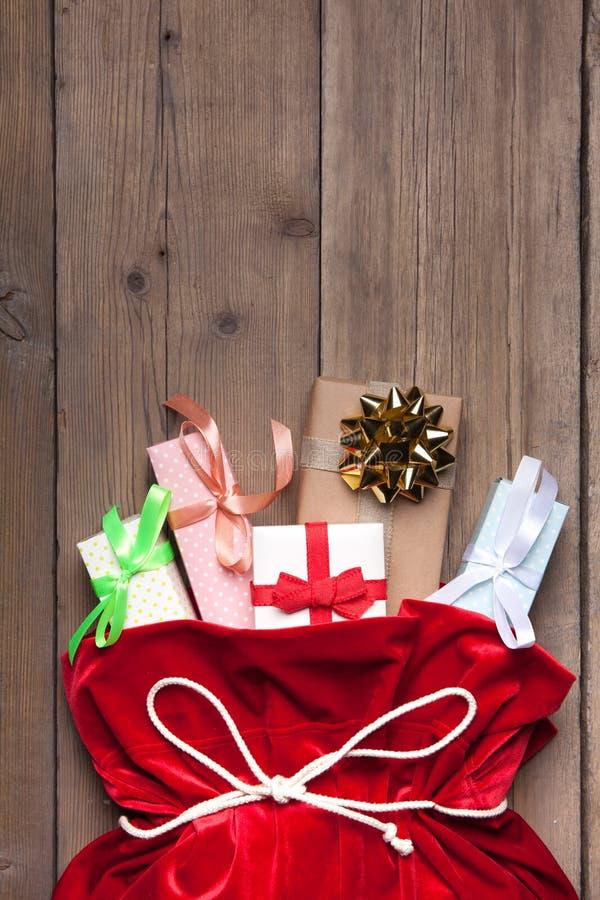 Święty Mikołaj torba Folująca Teraźniejszym prezenta pudełkiem, Czerwony boże narodzenie worek na Starym drewno ściany tle fotografia royalty free