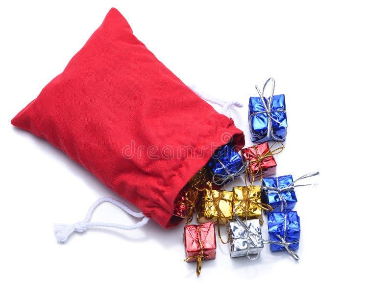 Święty Mikołaj torba teraźniejszość rozlewa za białej powierzchni dalej obraz stock