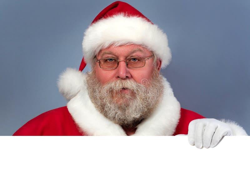 Święty Mikołaj trzyma białą deskę obraz royalty free