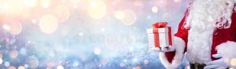 Święty Mikołaj Trzyma Prezent Świąteczny Z Śnieżnym Tłem zdjęcie royalty free
