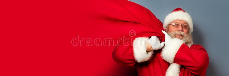 Święty Mikołaj trzyma torbę prezenty zdjęcia stock