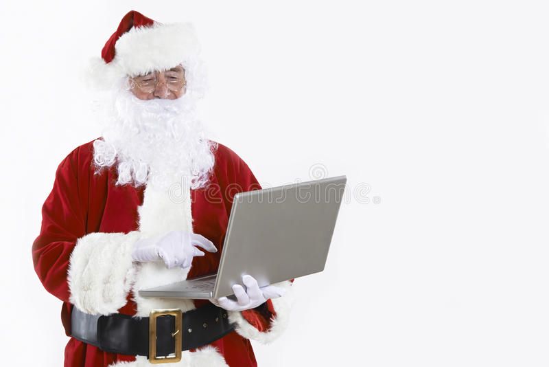 Święty Mikołaj Używa laptop Na Białym tle zdjęcie stock