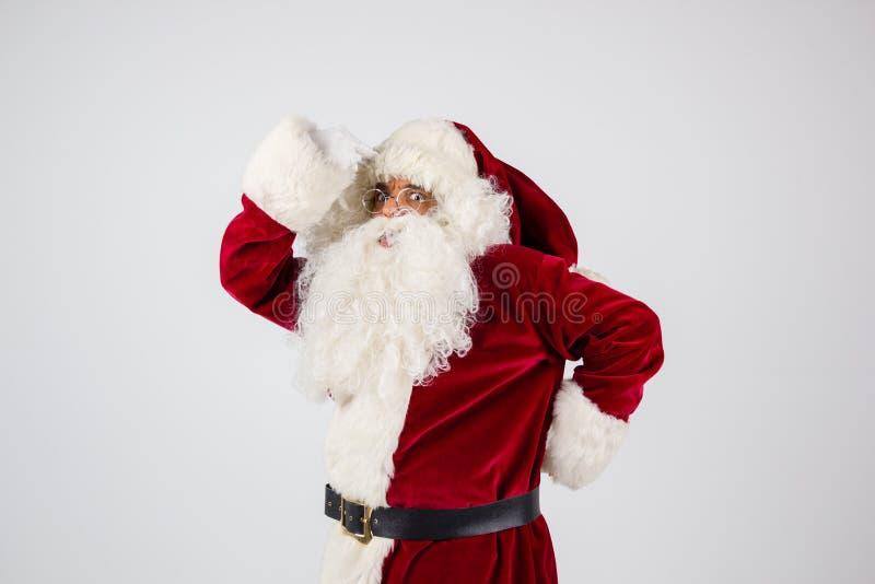 Święty Mikołaj w eyeglasses i czerwonych kostiumowych stawiać rękach na głowie zdjęcia stock