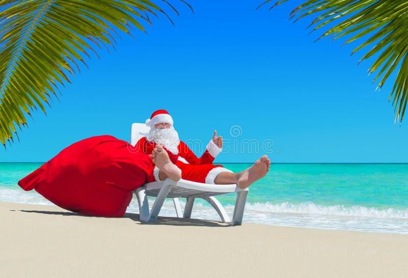 Święty Mikołaj z bożymi narodzeniami grabije na deckchair przy palmy plażą zdjęcia royalty free