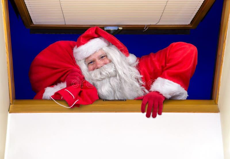 Święty Mikołaj z torbą wspina się okno obraz stock