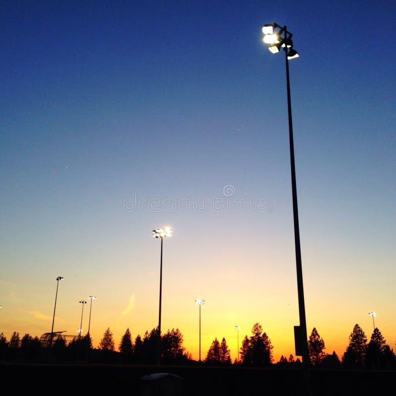 Światła przychodzi dalej nad sportów polami przy zmierzchem obraz stock