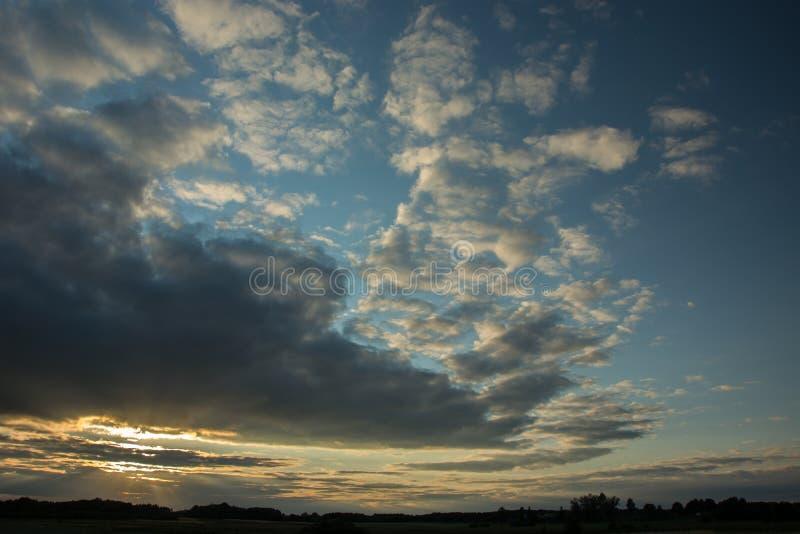 Światła słonecznego łamanie przez szarego wieczór chmurnieje w niebie, linia horyzontu i drzewie, zdjęcie royalty free