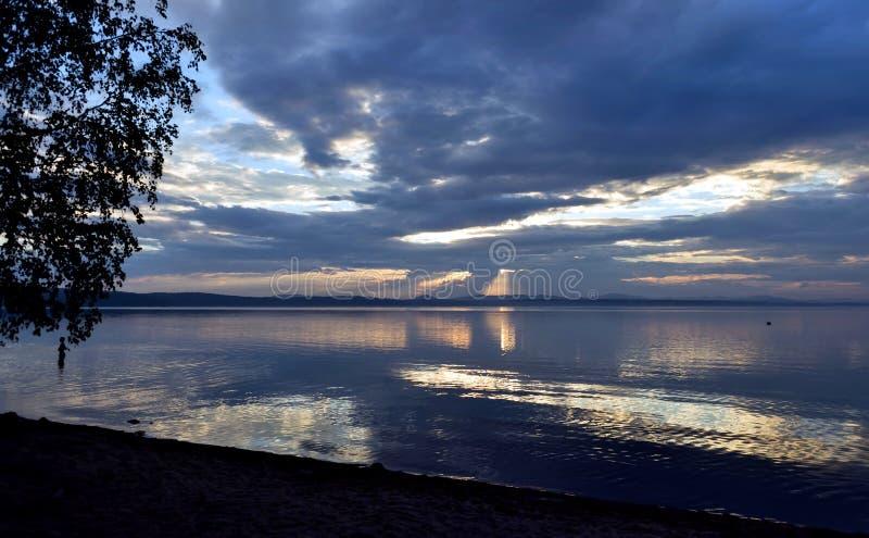 Światła słonecznego łamanie przez szarość chmurnieje nad jeziorem zdjęcia royalty free