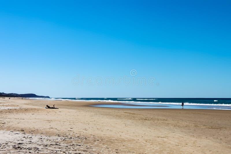 Światła słonecznego wybrzeża plaża w Australia z unreognizable ludźmi sylwetkowymi w odległości wliczając jeden mężczyzna na lapt obrazy stock