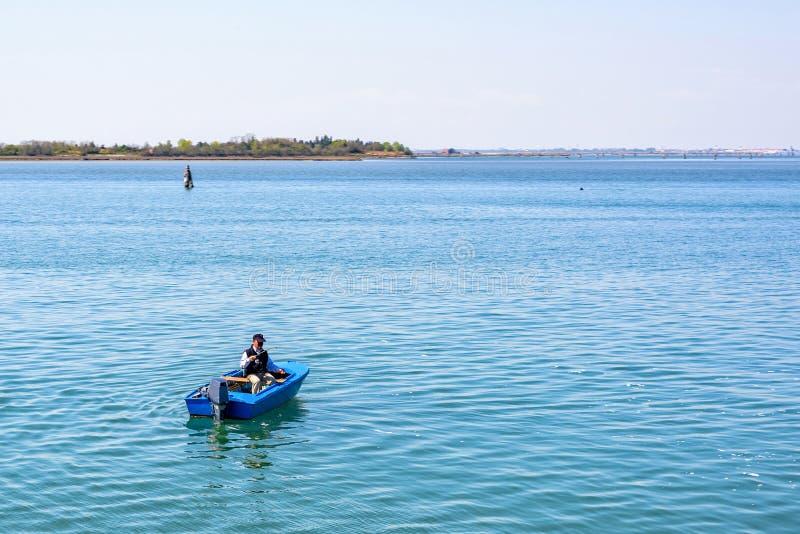 Światło dzienne widok rybak w błękitnym łódkowatym narządzanie połowu prąciu zdjęcia stock