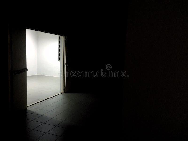 Światło od drzwi w datk pokoju obraz royalty free