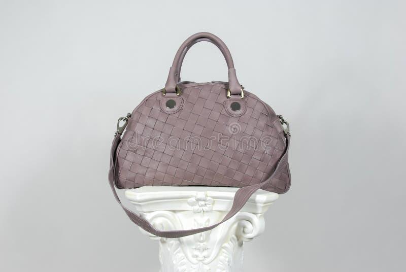 Światło - purpurowego zamszowy rzemienna torebka na greckiej kolumnie zdjęcie stock