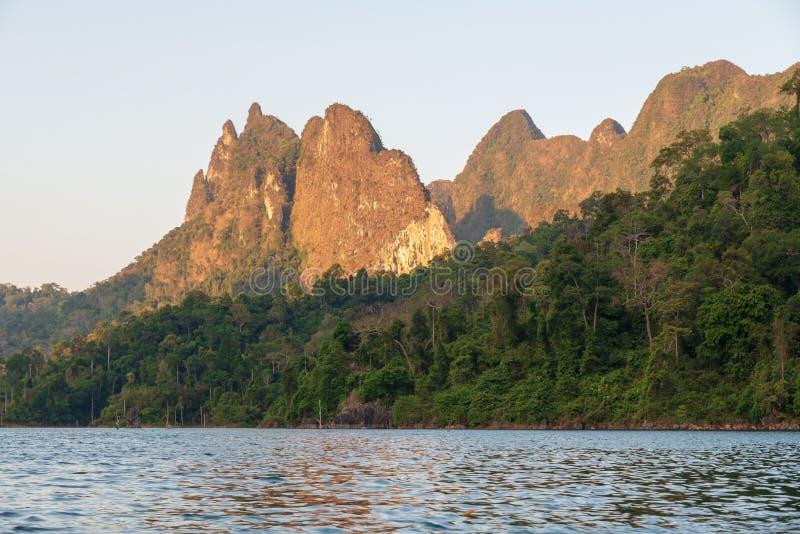 Światło słoneczne błyszczy przez gór i lasu na rzece zdjęcia stock