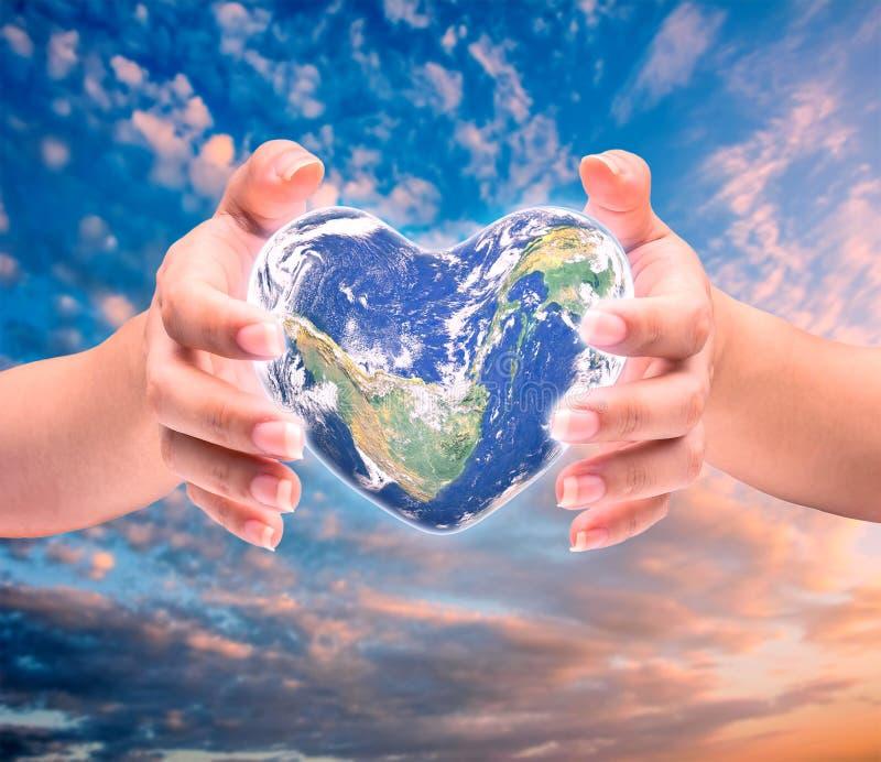 Świat w kierowym kształcie z nadmiernymi kobiety istoty ludzkiej rękami zdjęcia stock