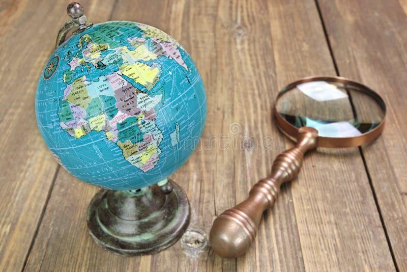 Światowa Geographical kula ziemska I Magnifier Na Drewnianym stole obrazy royalty free
